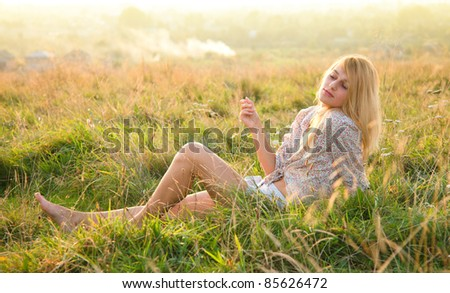 Beautiful girl is relaxing while sitting on green field - stock photo