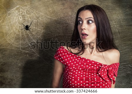 Beautiful girl is scared of a spider - stock photo