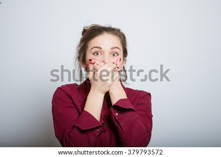 Beautiful girl is shocked, covering her mouth, isolated on a gray background