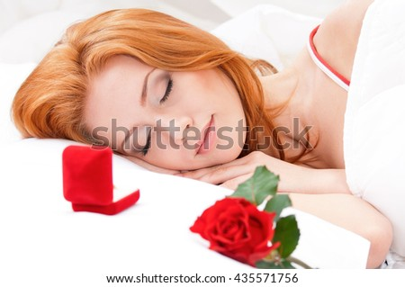 Beautiful girl is sleeping on white bed. Wedding ring in a gift box on a pillow next to her - holidays and happiness concept.