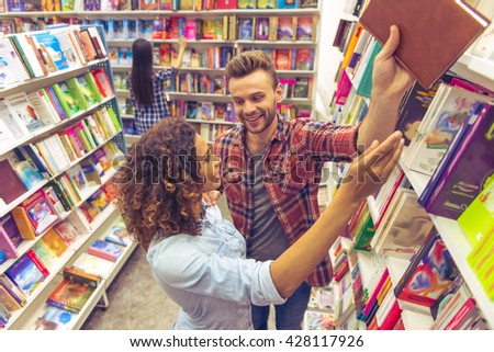 Beautiful girl is smiling and asking handsome guy to take book from upper shelf in the bookshop, another girl in the background - stock photo