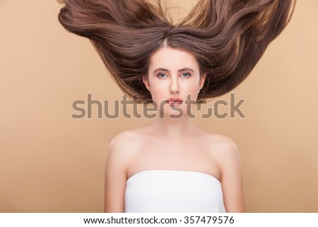 Beautiful girl is standing with her long hair blowing by wind. She is looking at camera with desire. The lady is wearing a white towel. Isolated on brown background - stock photo