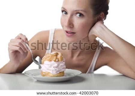 Beautiful girl is tasting puff. - stock photo