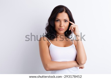 Beautiful girl is thinking about something carefully. She is focusing at it strongly. She is raising her finger to her temple. Isolated and there is copy space in left side - stock photo