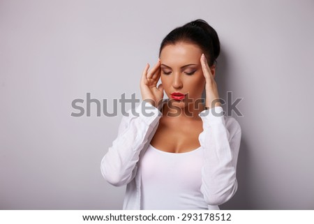 Beautiful girl is touching her temples with both her hands. She feels pain in her head. Her eyes are closed. Isolated and there s copy space in left side - stock photo