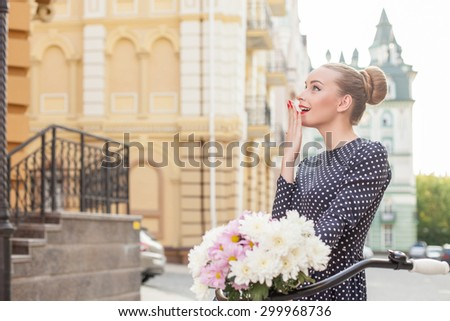 Beautiful girl is walking with bicycle across city. She is looking aside with surprise and smiling. The lady is covering her mouth with her palm with amazement. Copy space in left side - stock photo