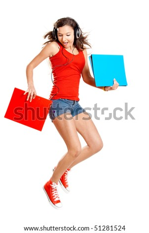 Beautiful girl jumping and listen music while holding some cases, isolated on white - stock photo