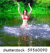 beautiful girl jumping with splashes in sexy red swimwear - stock photo
