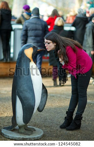 Beautiful girl kissing a giant Penguin - stock photo