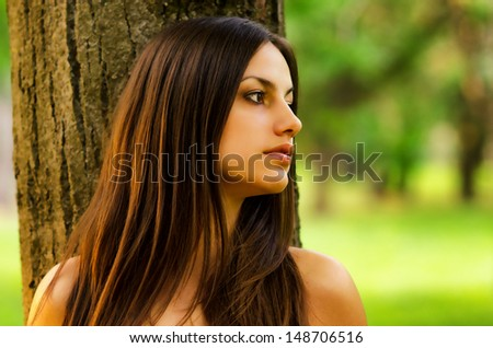 Beautiful girl leaning against the tree in the forest. - stock photo