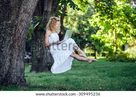 beautiful girl levitates in nature with laptop