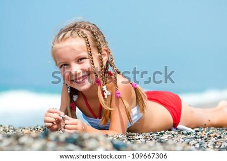 beautiful girl lies on a beach on the coast - stock photo