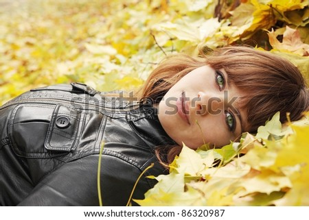 beautiful girl lies on yellow maple leaves - stock photo