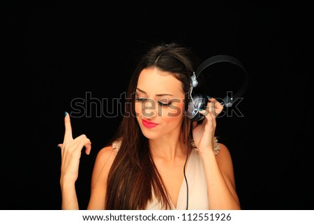 Beautiful Girl listening music over black background - stock photo