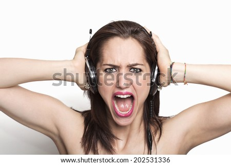 Beautiful girl listening to music and screaming - stock photo