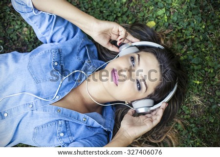 Beautiful girl listening to music in a park with headphones