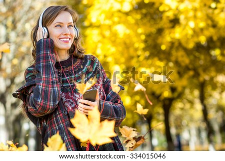 Beautiful girl listening to music in autumn landscape golden park with flying maple leaves, copy space - stock photo
