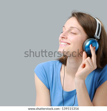 Beautiful girl listening to music on headphones - stock photo