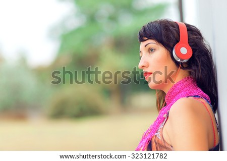 Beautiful girl listening to music on headphones. Young woman listening to music - stock photo