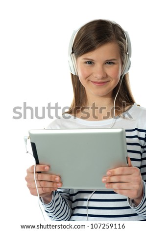 Beautiful girl listening to music via wireless tablet wearing headphones and smiling - stock photo