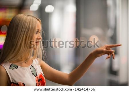 Beautiful girl looking in the shopwindow on the night city street - stock photo