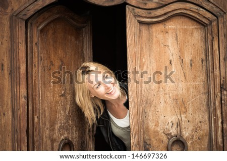 Beautiful girl looks out of the door - stock photo