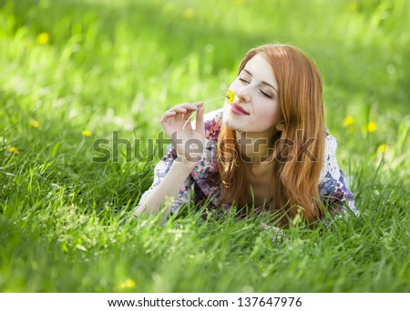 Beautiful girl lying down at grass.