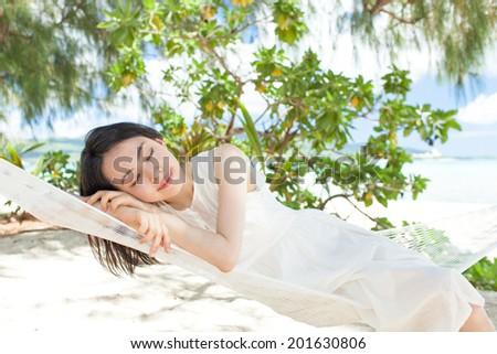 beautiful girl lying in a hammock on the tropical island beach - stock photo