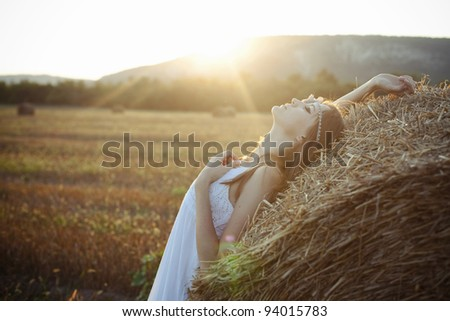 beautiful girl lying on a haystack with my eyes closed at sunset - stock photo