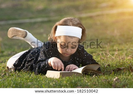Beautiful girl lying on grass and read book, against green of summer park.  - stock photo