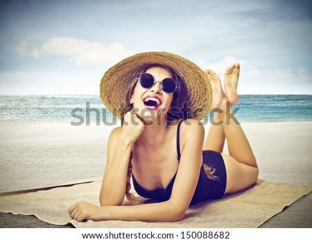 beautiful girl lying on the beach with straw hat and swimsuit - stock photo
