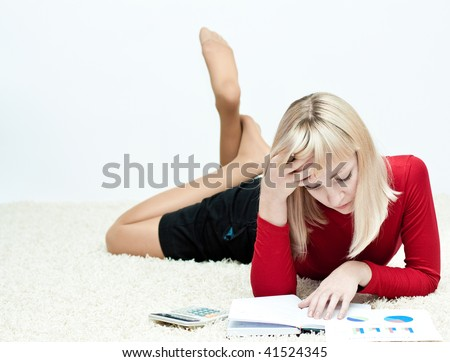 Beautiful girl lying on the floor and planing a budget with calculator and some reports - stock photo
