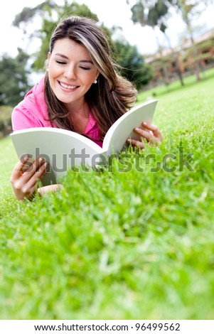 Beautiful girl lying outdoors and reading a book