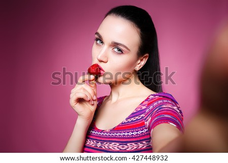 beautiful girl makes selfie and eating strawberries. the concept of fun and healthy food. pink background - stock photo