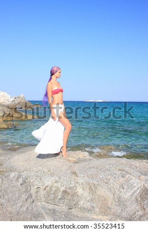 Beautiful girl meditating on the beach in Greece