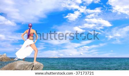Beautiful girl meditating on the beach in Greece - stock photo