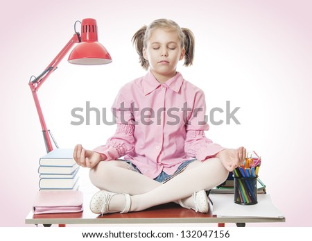 Beautiful girl meditating on the desk - stock photo