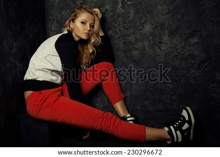 Beautiful girl model. Fashion portrait of stylish blond girl in trendy red pants, black and white sweater and sneakers.  Smoky eyes make up.