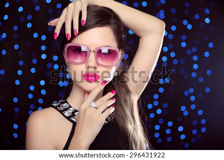 Beautiful  Girl Model in fashion sunglasses with pink lips, manicured polish nails and luxury gemstone necklace over party holiday lights background.