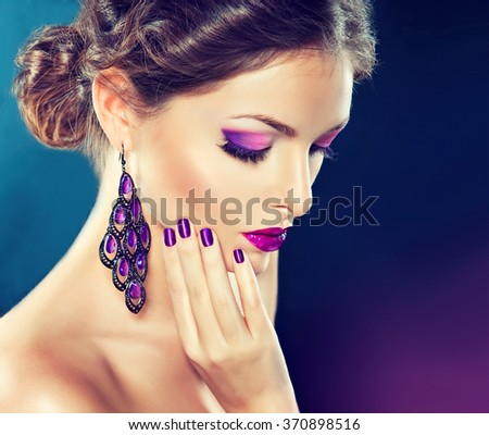 beautiful   girl model with fashion make-up and purple manicure on nails . Jewelry and cosmetics , large violet earrings - stock photo