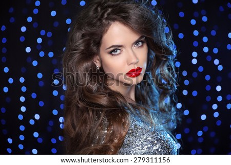 Beautiful girl model with long brown curled hair and red lips over holiday dark background with blue bokeh lights. Glamour lady.