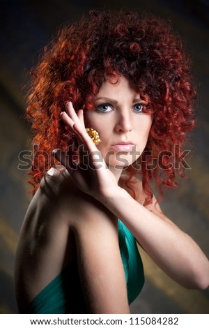 Beautiful girl model with red hair pose on gray background