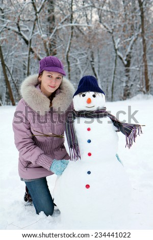 Beautiful girl near a snowman - stock photo