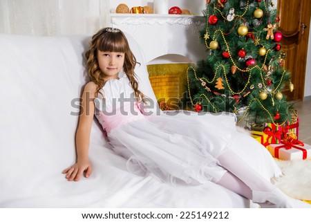 Beautiful girl near the decorated Christmas tree - stock photo