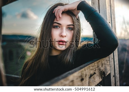 Beautiful girl near the wooden structure. What leaned on the arm. Cold colors and charming background. Autumn time.
