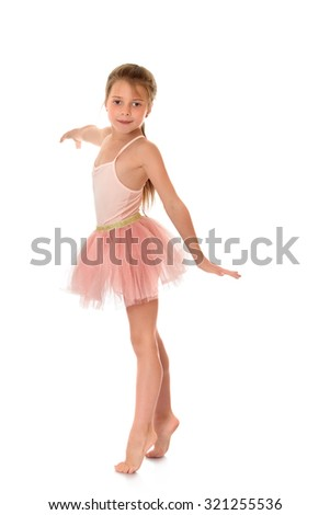 Beautiful girl of school age in a pink dress ballerina. The girl opened his arms to the side and standing barefoot on tiptoes on the floor-Isolated on white background