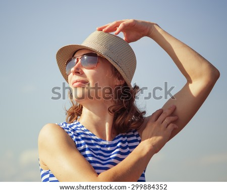 Beautiful girl on a beach in sunglasses and a hat.