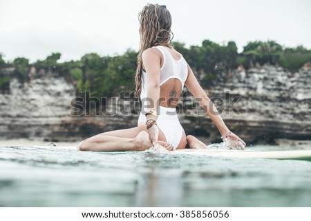 Beautiful girl on a surf board in the ocean. Girl with long hair in a white bathing suit in the ocean on the longboard. beautiful girl with a tattoo on his back in the ocean surf. - stock photo