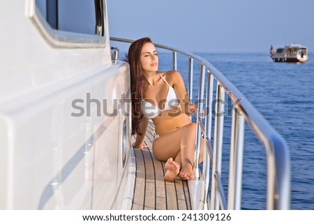 Beautiful girl on a yacht in the sunshine is resting eyes closed - stock photo