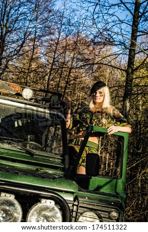Beautiful girl on camouflage outfit and the off-road vehicle - stock photo